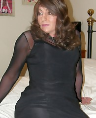 Gorgeous brunette crossdresser teasing in a pair of black nylons and matching dress to finish you off
