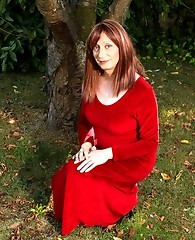 Lucimay posing outdoors in a gorgeous long red dress