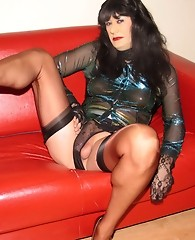 Yvette posing on a red leather sofa and showing her cock